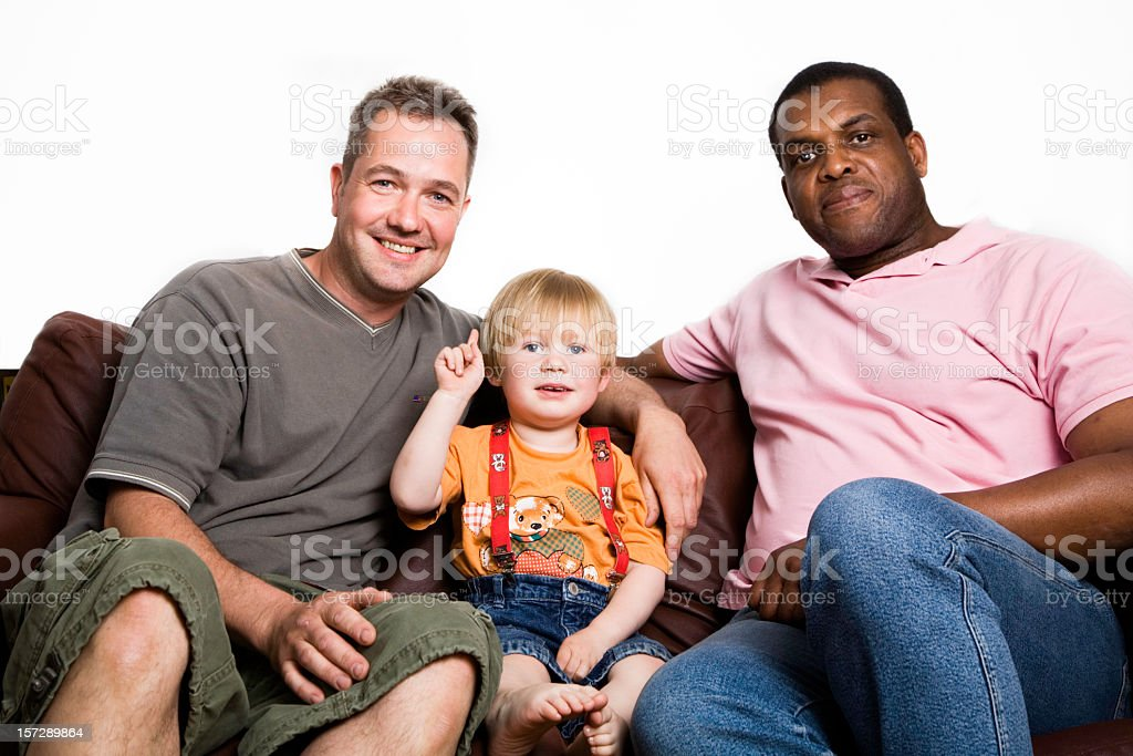 Unconventional multiracial family two men, boy sitting on sofa smiling. royalty-free stock photo
