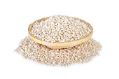 uncooked barley grain in bamboo basket with white background