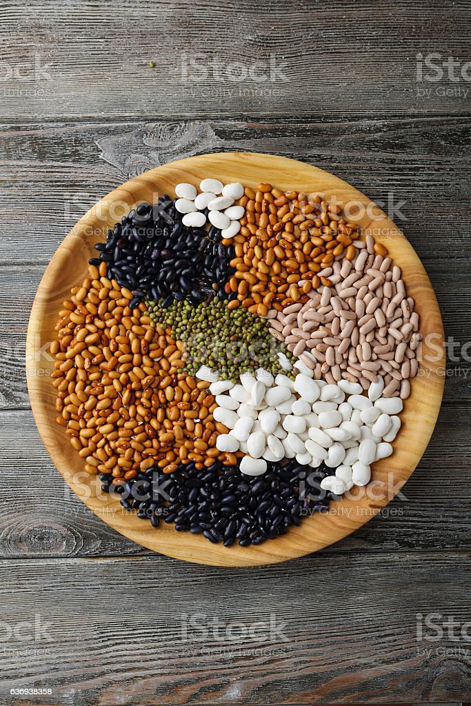Uncooked beans on wooden plate stock photo
