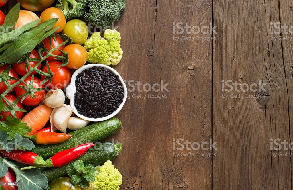 Uncooked black rice in a bowl with vegetables stock photo