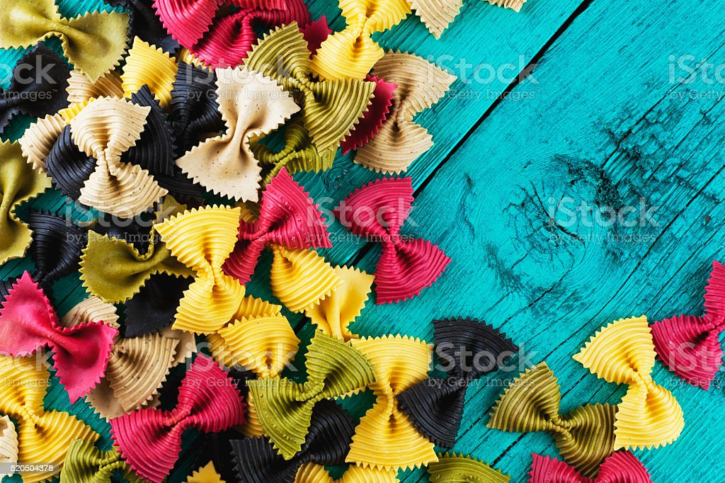 Uncooked butterfly colorful pasta on wooden background stock photo