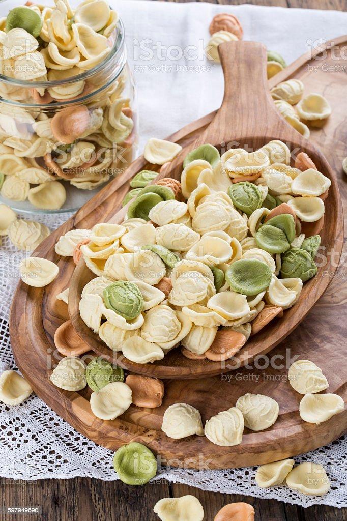 Uncooked colorful orecchiette in a wooden bowl. Italian pasta. stock photo