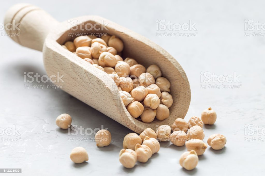 Uncooked dry chickpeas in a wooden scoop, horizontal stock photo