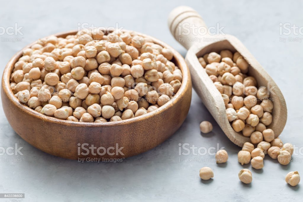Uncooked dry chickpeas in wooden bowl and in scoop, horizontal stock photo