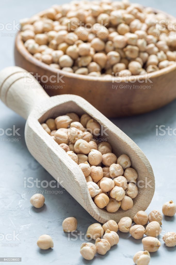 Uncooked dry chickpeas in wooden bowl and in scoop, vertical stock photo