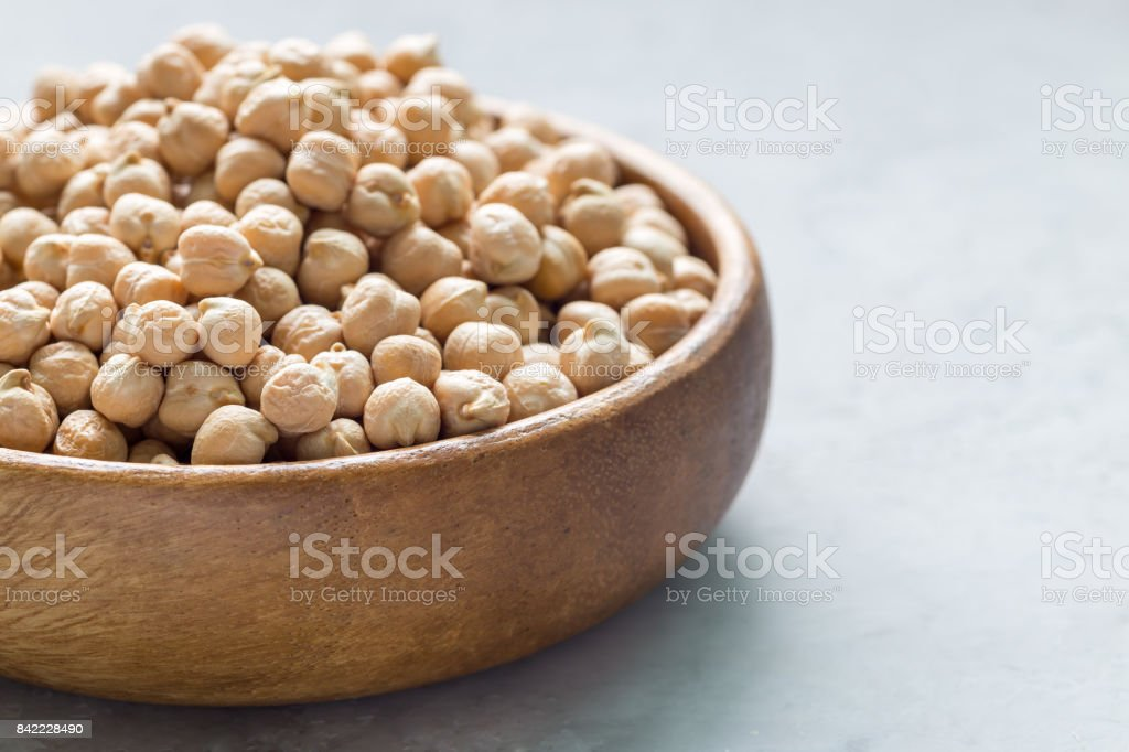 Uncooked dry chickpeas in wooden bowl, horizontal, copy space stock photo