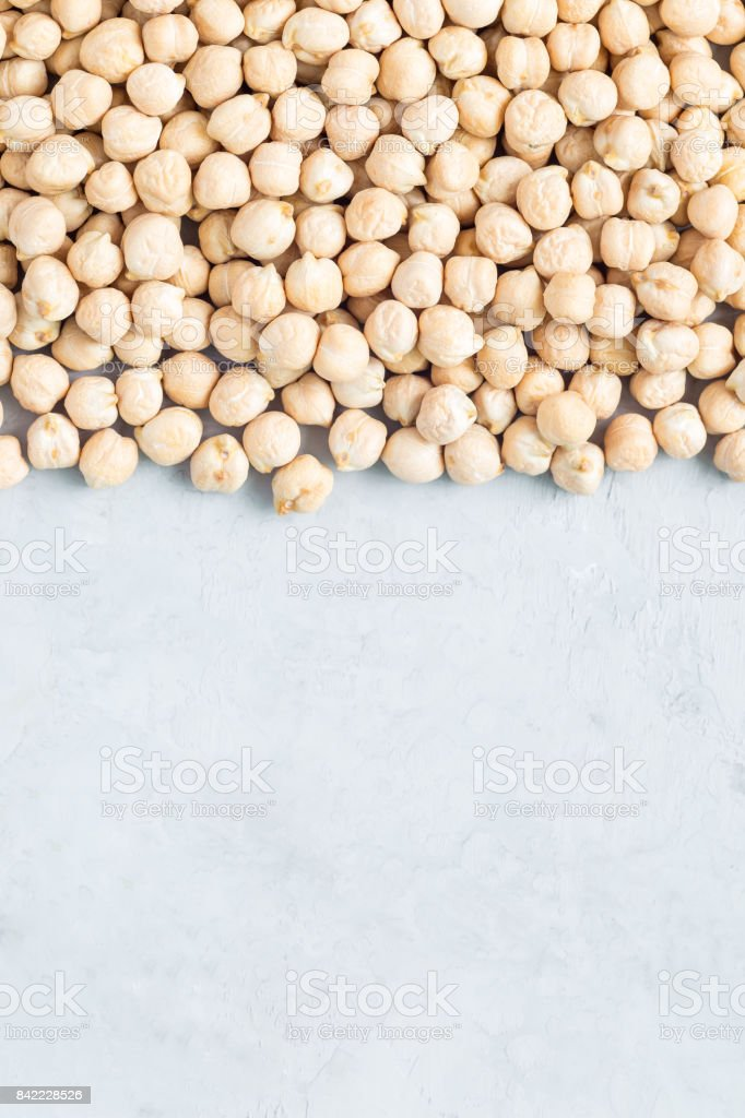 Uncooked dry chickpeas on concrete background, vertical, copy space stock photo