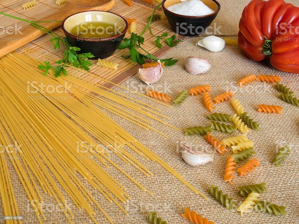 Uncooked seco espaguete em superfícies rústica com tomate, alho, foto royalty-free