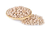 uncooked garbanzo bean on bamboo basket with white background