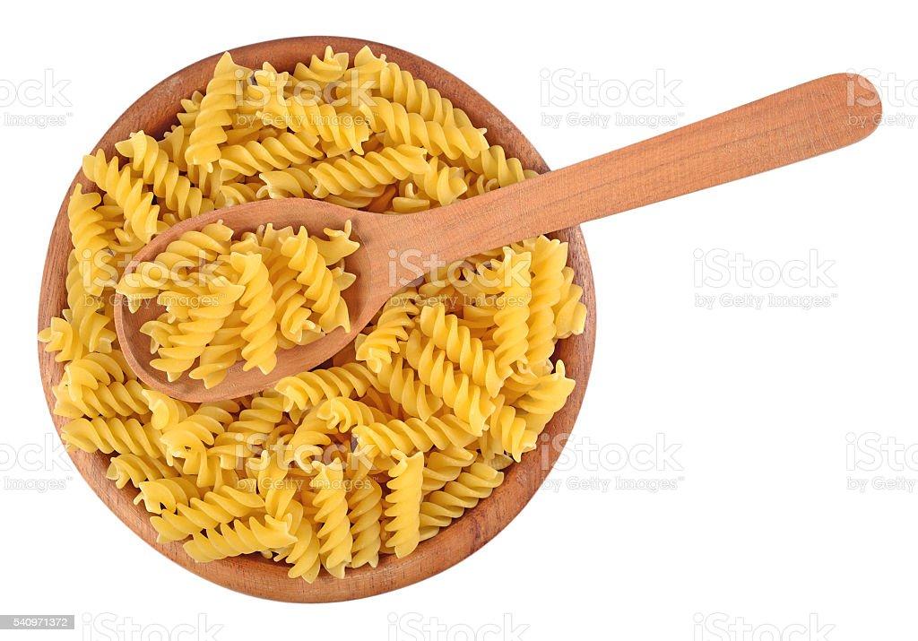 Uncooked italian pasta fusilli in a wooden bowl stock photo