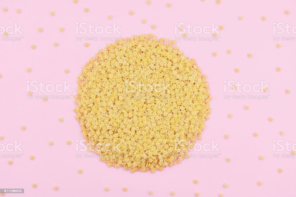 Uncooked italian pasta on pink trendy background. stock photo