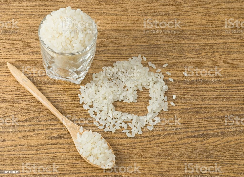 Uncooked Japanese Rice in A Wooden Spoon stock photo