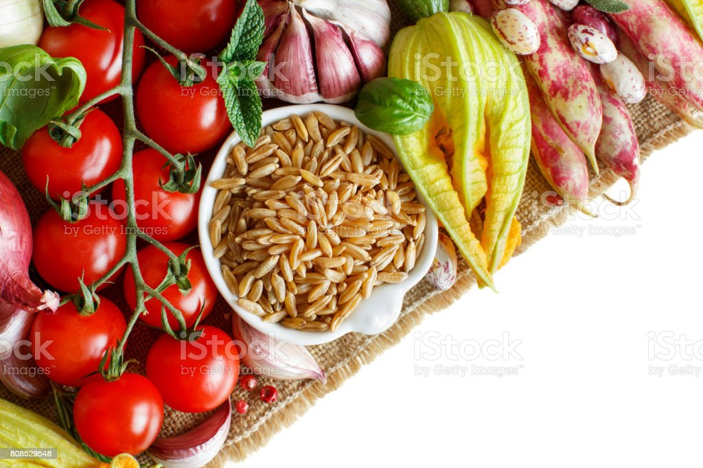 Uncooked kamut grain with vegetables stock photo