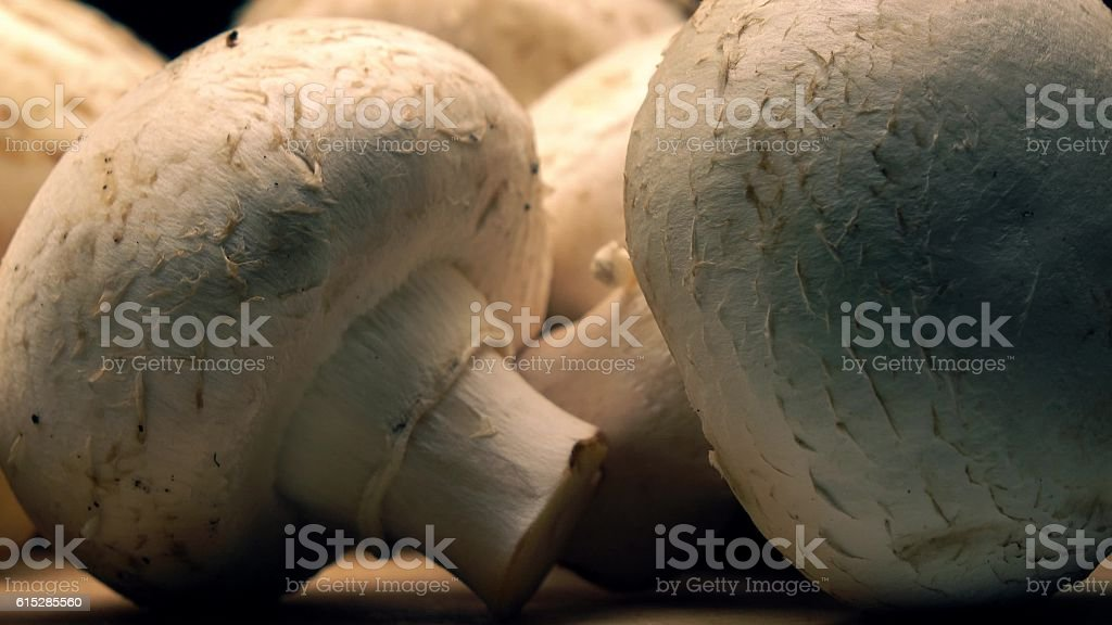 Uncooked mushrooms on wooden cutting board stock photo