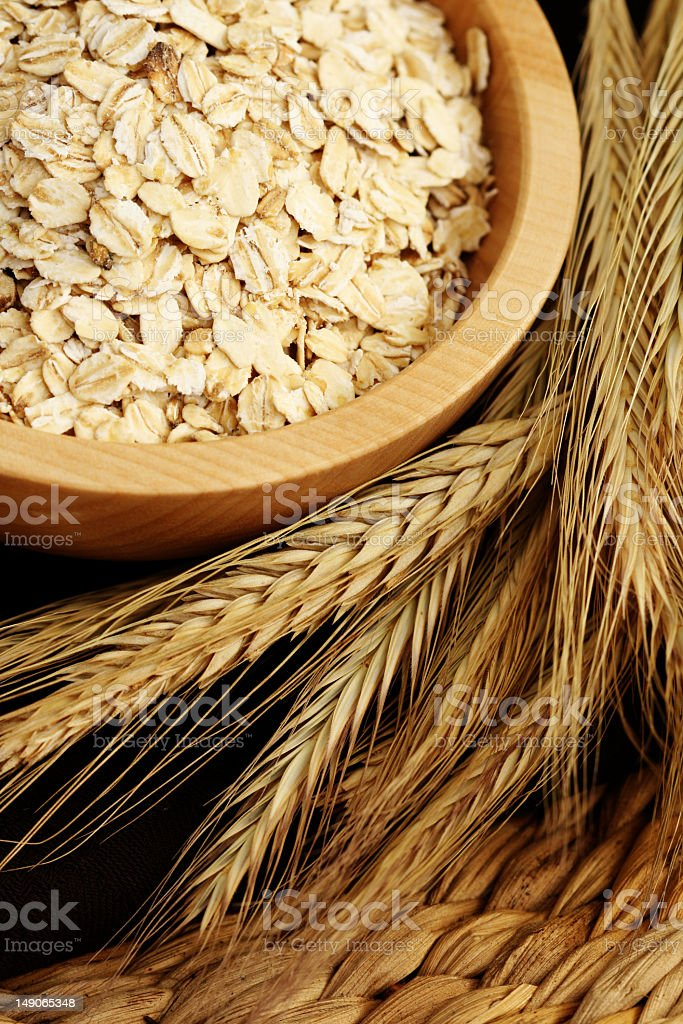 Uncooked oatmeal in a bowl with wheat stalks royalty-free stock photo