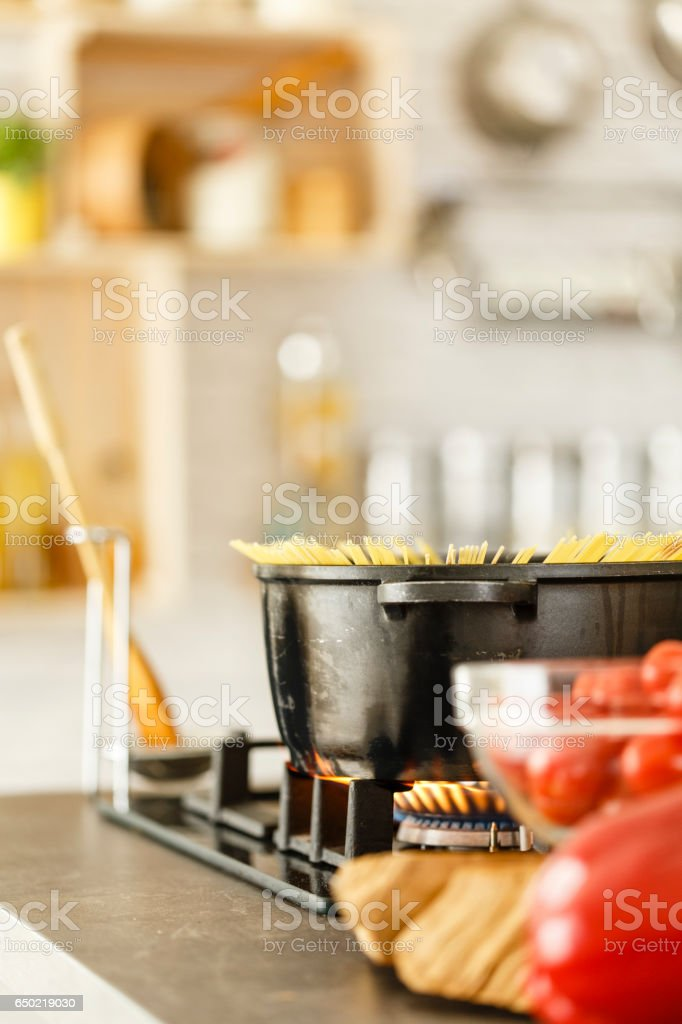 Uncooked pasta in pot on gas stove stock photo