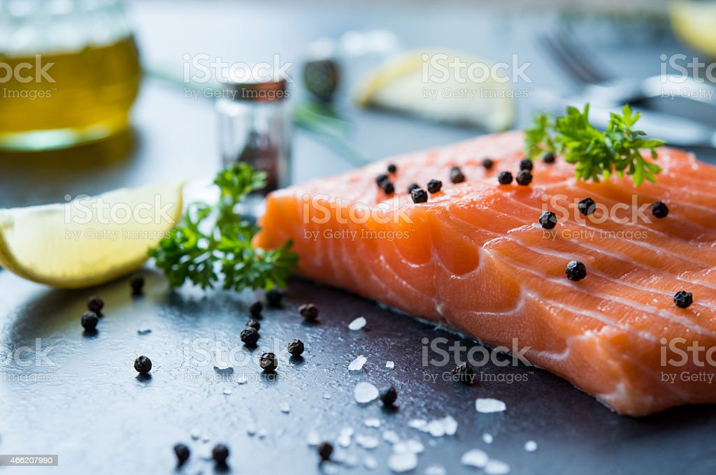 Uncooked salmon on a black counter covered in seasoning stock photo
