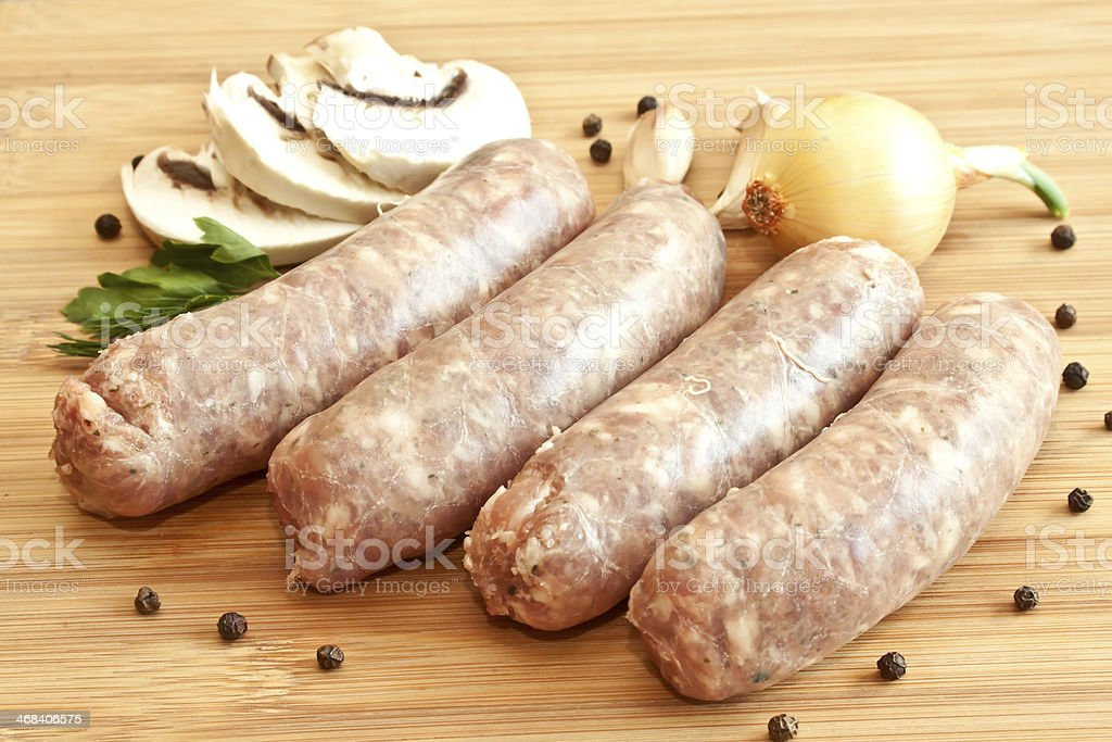 Uncooked sausages with vegetables on the chopping board royalty-free stock photo
