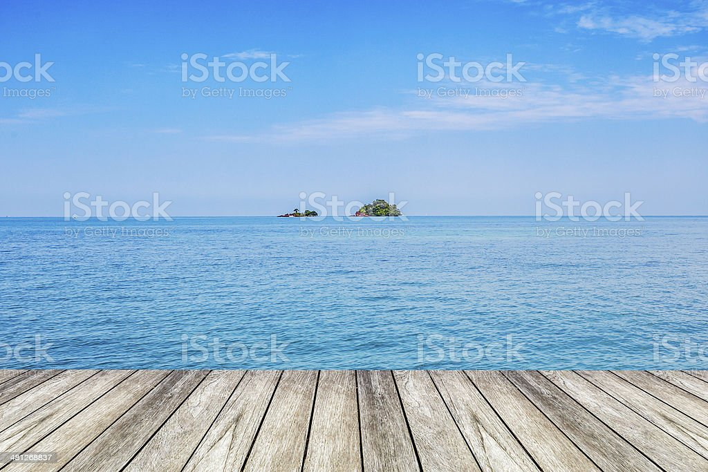 Under blue sky, wood platform beside the sea. stock photo