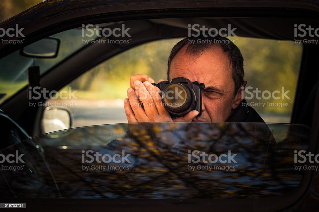 undercover man hidden in car take photo stock photo