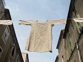 Undergarment shirt  hanging on a clothesline between the buildings