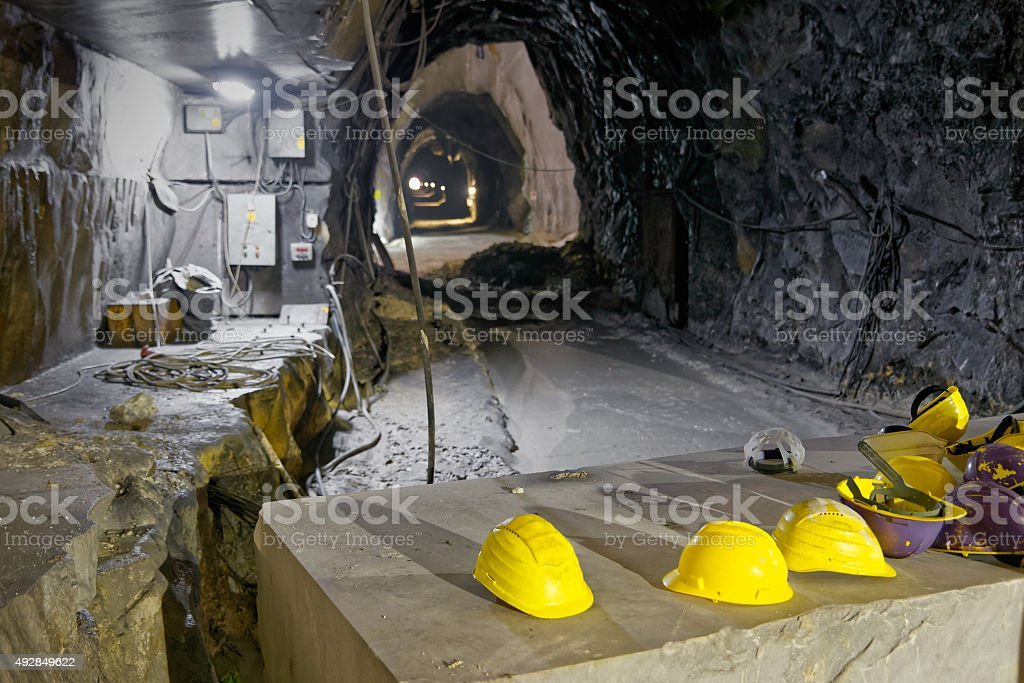 Underground mine in the Apuan Alps, group of yellow hats stock photo