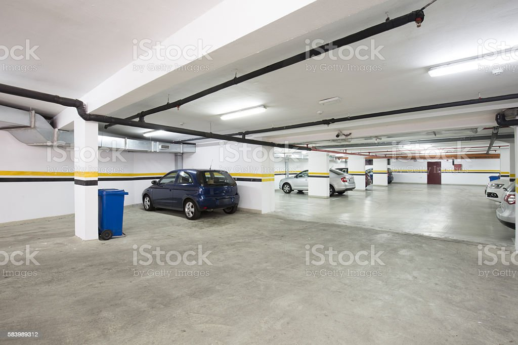 Underground parking lot, interior with a few parked cars. stock photo