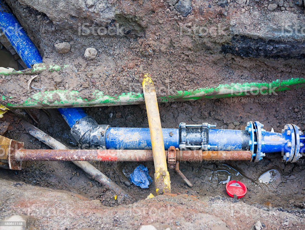 Underground pipe repair work trench stock photo