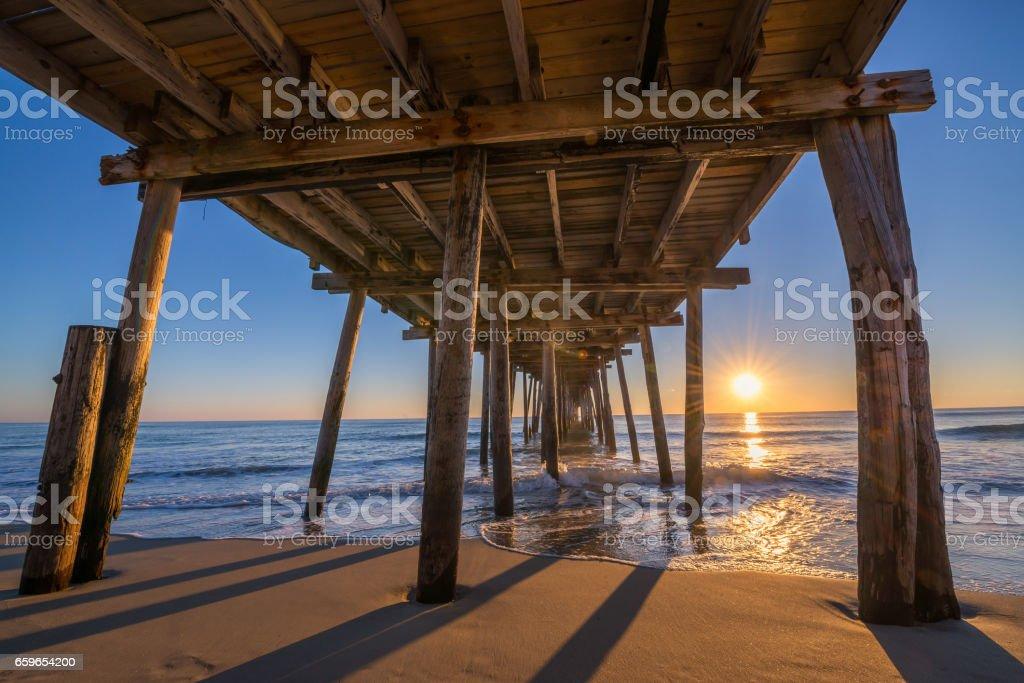 Underneath Nags Head Pier at sunrise stock photo