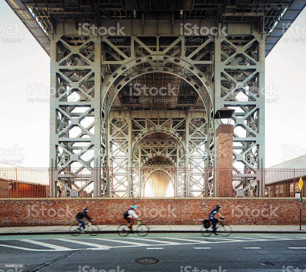 Underneath the Brooklyn Williamsburg bridge morning with bikers stock photo