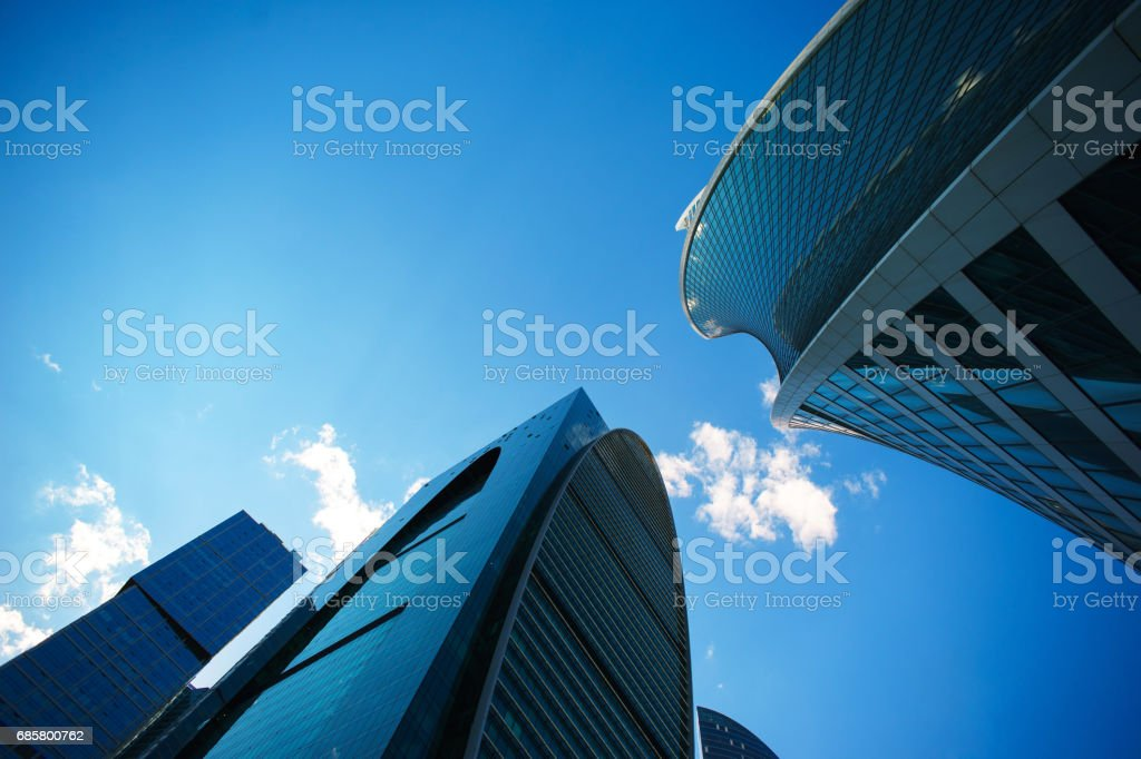 Underside angle view to background of modern glass building skyscrapers over blue sky stock photo