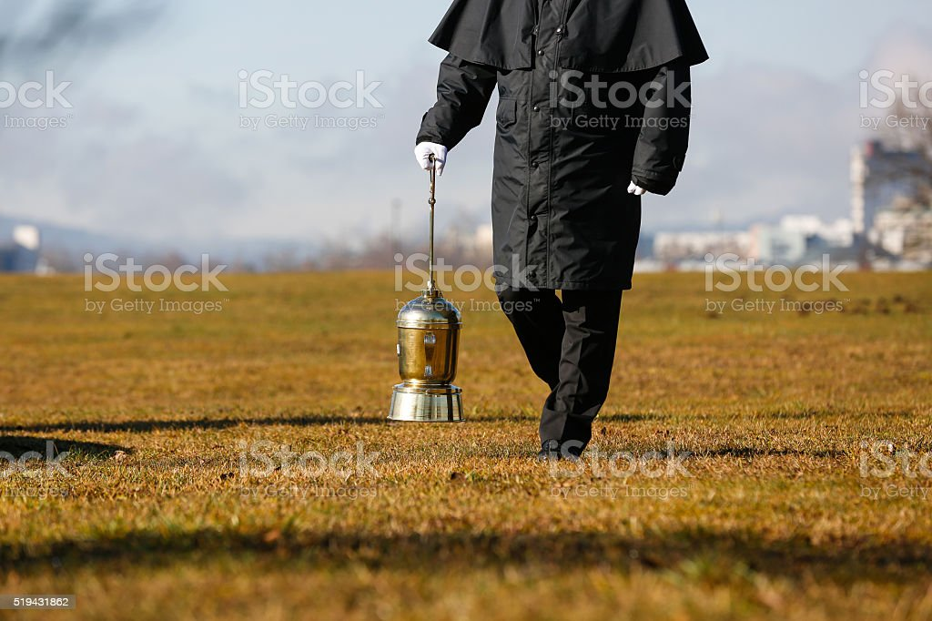 Undertaker carrying an urn with ashes of cremated human stock photo
