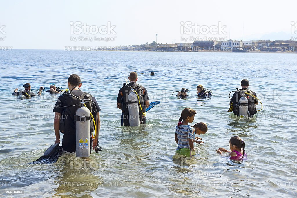 Underwater divers and children enjoy the Red Sea. stock photo
