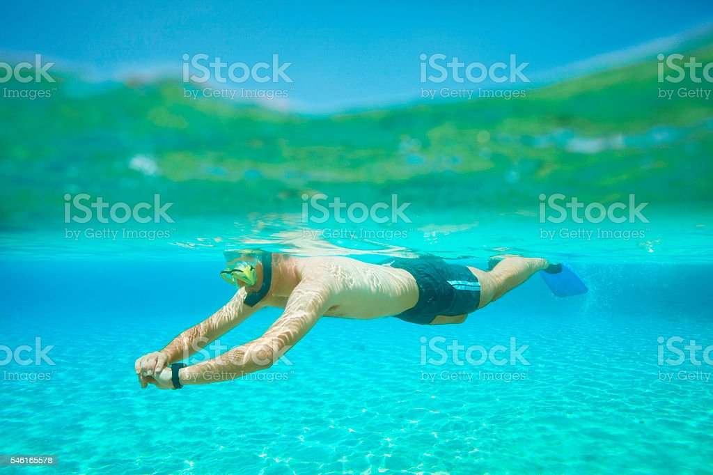 Underwater diving adventure  Young man snorkeling   Half-half  turquoise sea lagoon stock photo
