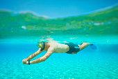 Underwater diving adventure  Young man snorkeling   Half-half  turquoise sea lagoon