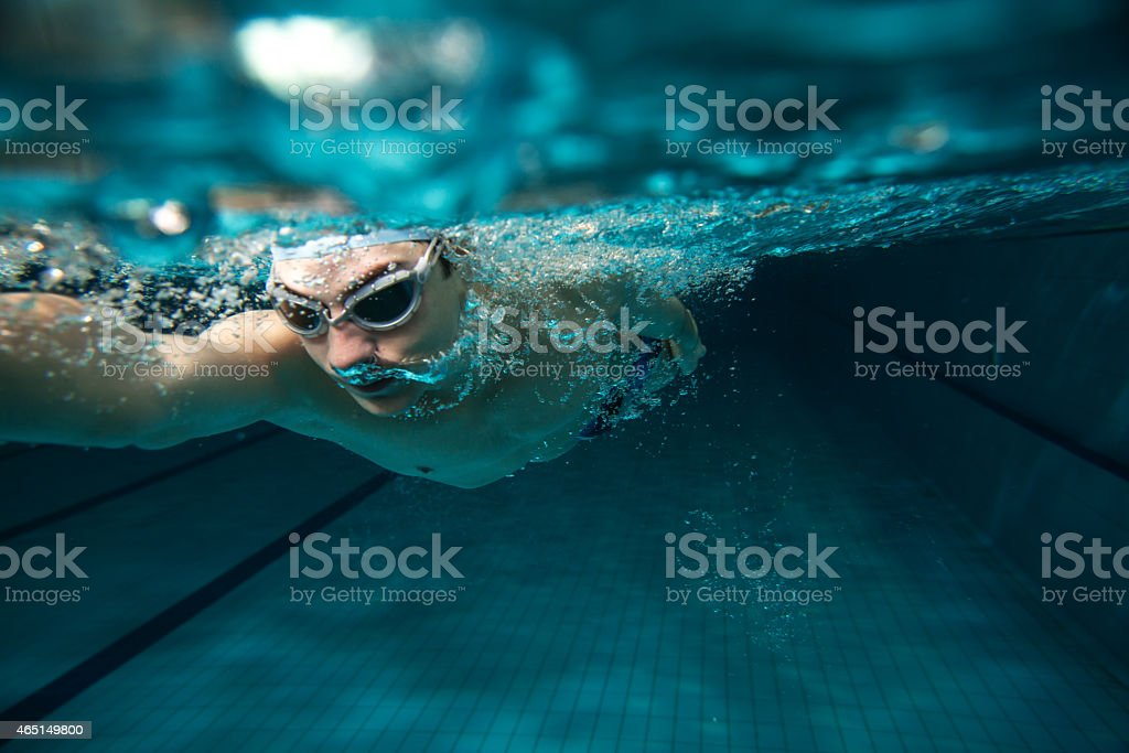 Underwater photo of a man swimming in a pool stock photo