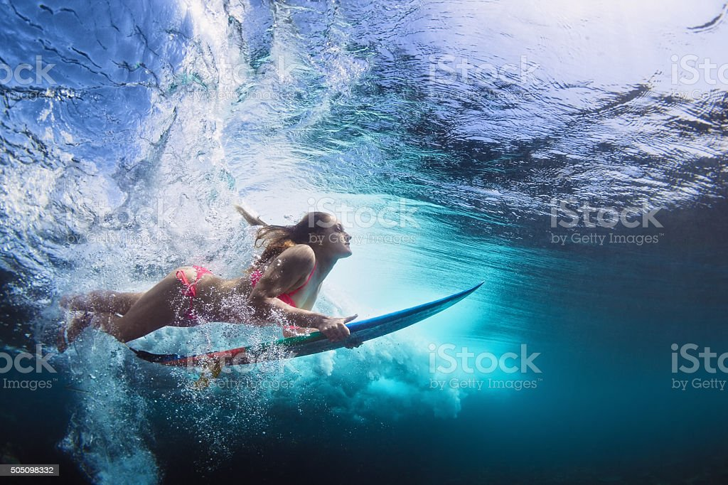 Underwater photo of girl with board dive under ocean wave stock photo