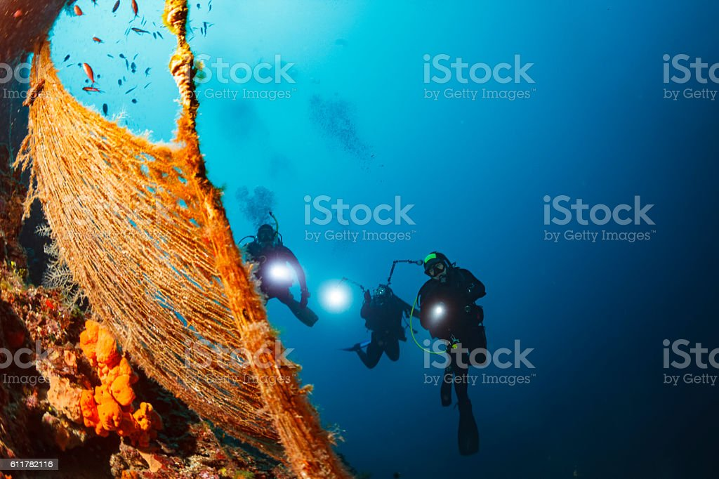 Underwater photographer  Scuba divers photographing  Explore reef   Old fishing net stock photo
