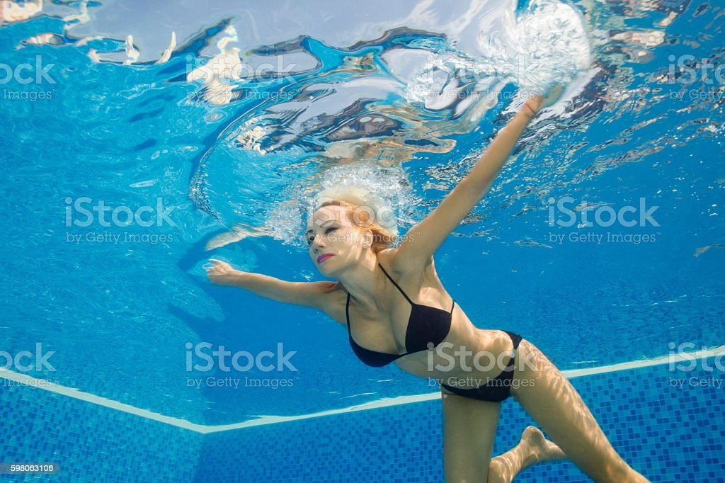 Girl swimming underwater containing bubbles, pool, and