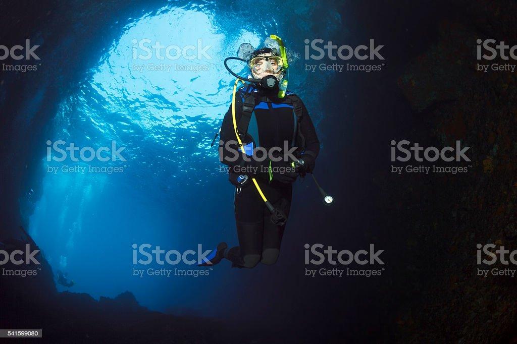 Underwater  Scuba divers enjoy  Explore  underwater cave stock photo
