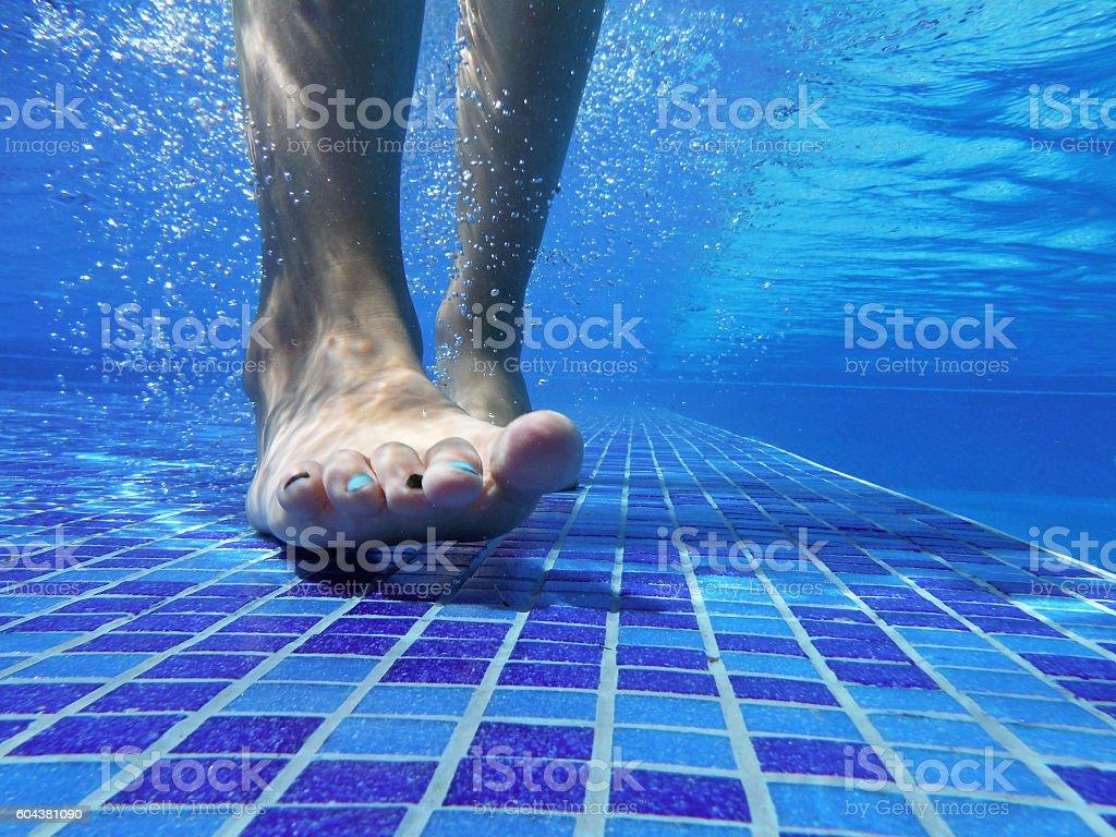 Underwater shot of feet on pool bottom stock photo