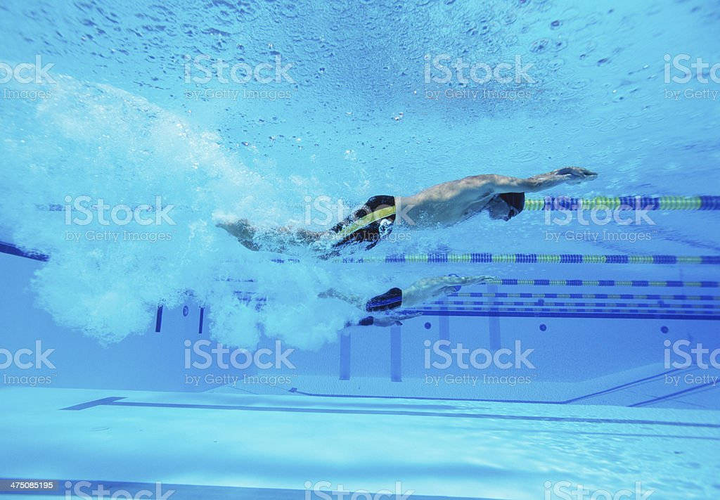 Underwater shot of three male athletes racing in swimming pool royalty-free stock photo