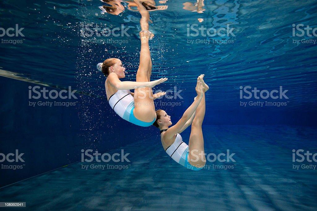 underwater synchronised swimming training stock photo