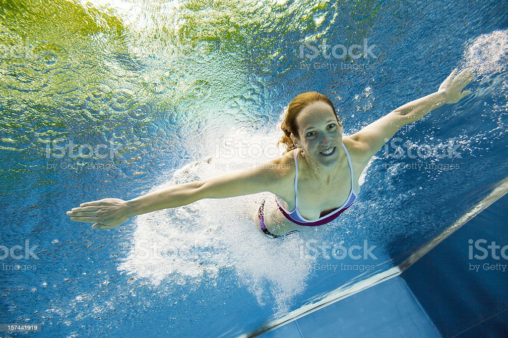 underwater view of a young woman jumping into the water royalty-free stock photo