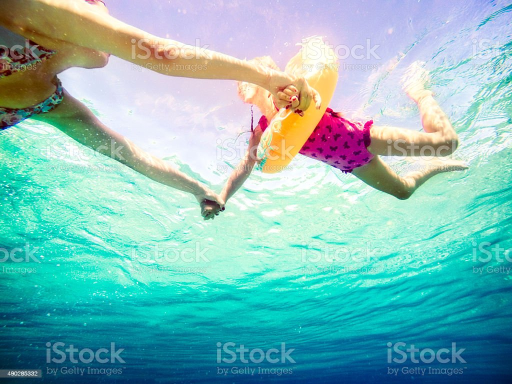 Underwater view of family swiming in sea and holding hands stock photo