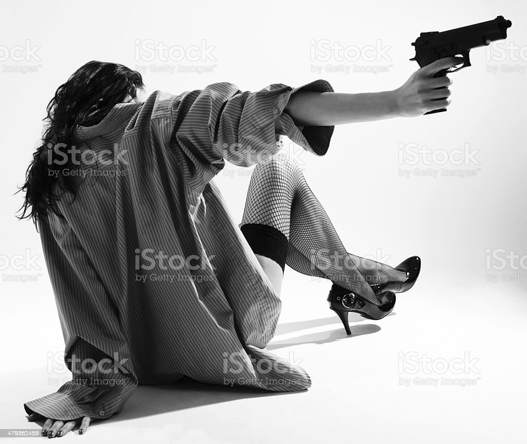 Undressed girl sits back and aims with handgun royalty-free stock photo