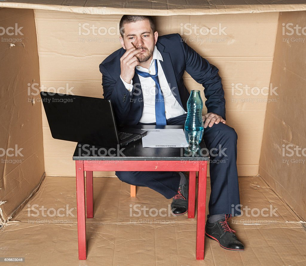 Unemployed businessman smokes and drinks alcohol stock photo