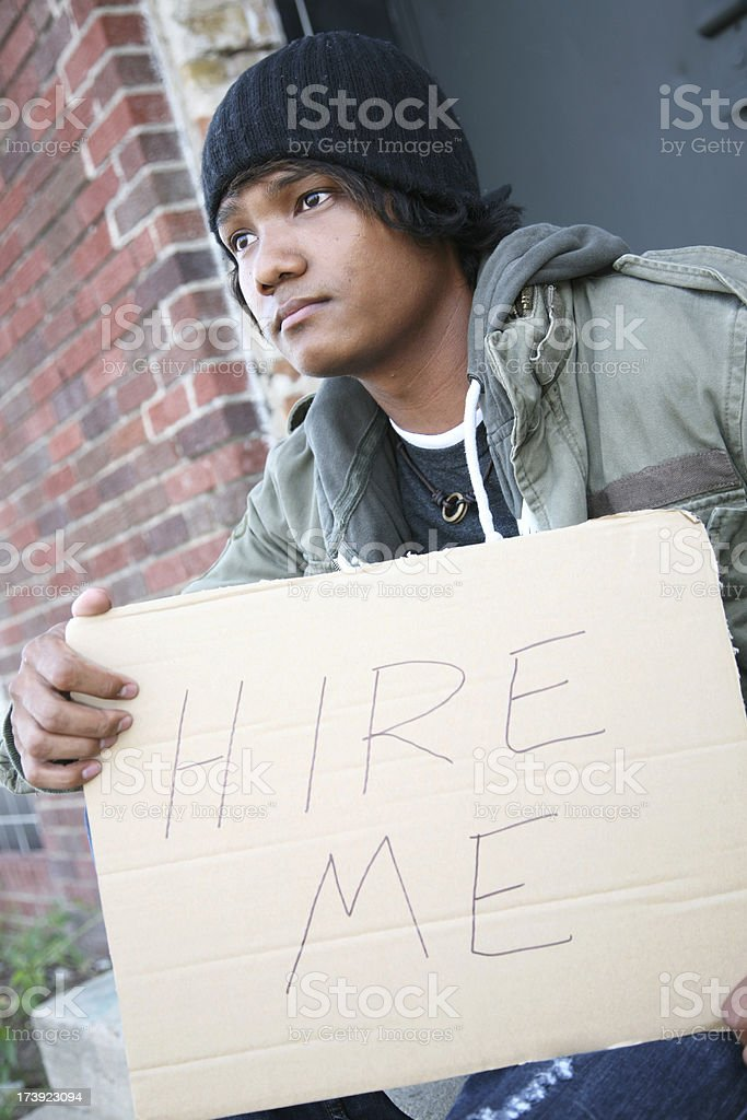 Unemployed Vet With a Hire Me Sign Looking Away royalty-free stock photo