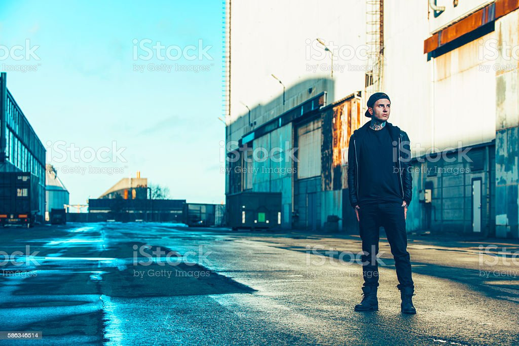 Unemployed young adult stands alone outside in industrial area stock photo
