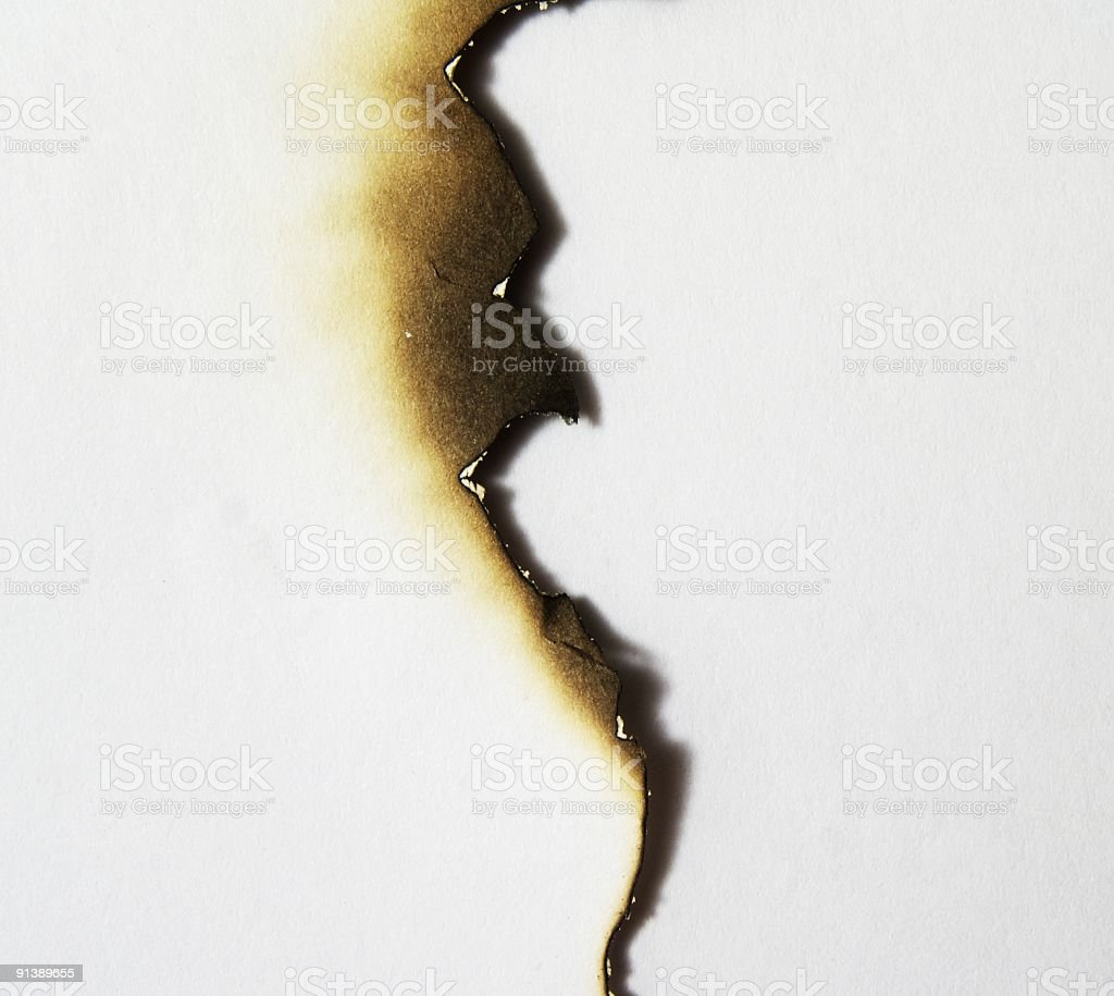 Uneven burned edge of a piece of paper stock photo